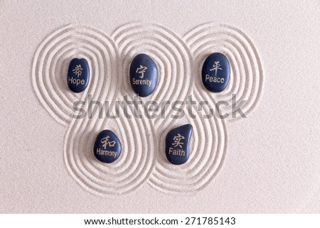 Zen art with stones on golden sand surrounded by a swirling infinite pattern of raked lines symbolizing peace, harmony, faith, hope and serenity, overhead view with copy space - stock photo