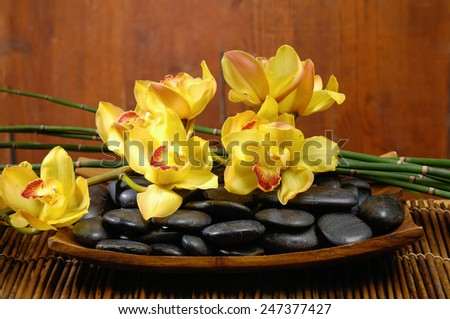 zen basalt stones with yellow orchid on bowl, bamboo grove on mat - stock photo