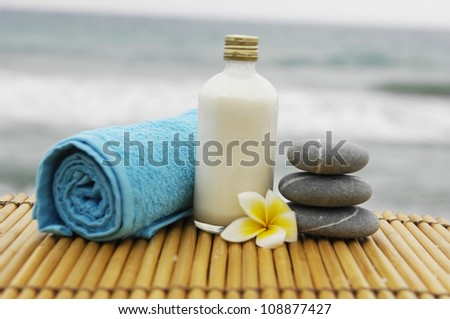 Zen concept �blue towel and salt in a glass with frangipani flower on mat - stock photo