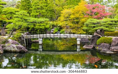 Zen garden pond with bridge and carp fish in Japan. - stock photo