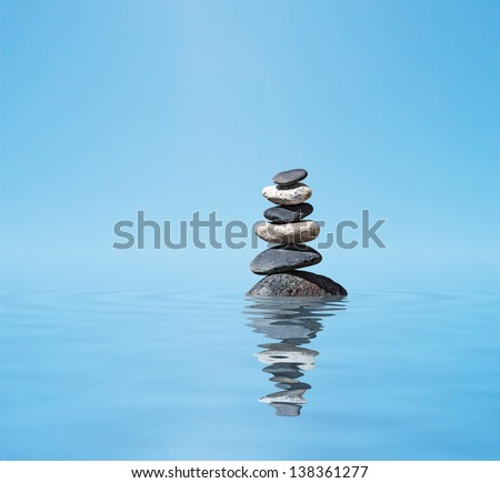 Zen meditation background -  balanced stones stack in water with reflection - stock photo