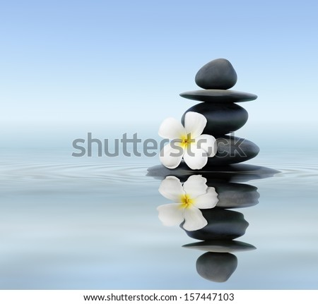 Zen spa concept background - Zen massage stones with frangipani plumeria flower in water reflection - stock photo