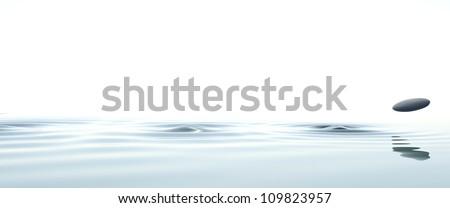 zen stone thrown on the water on white background - stock photo