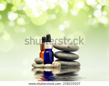 Zen stone with spa oil over green bokeh - stock photo