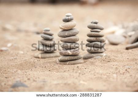 Zen stones garden, Spa stones treatment scene, zen like concepts, Stones pyramid on sand symbolizing zen, harmony, balance, series - stock photo
