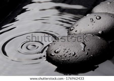 Zen stones on wet black background - stock photo