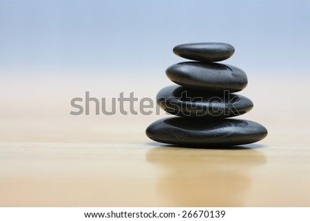 Zen stones on wooden surface. Shallow DOF. - stock photo