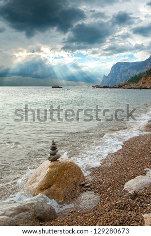 Zen stones pyramid by the sea, mountain and sun rays on background - stock photo
