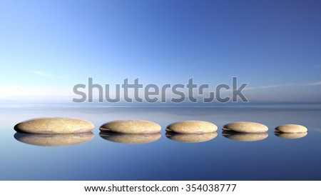 Zen stones row from large to small  in water with blue sky and peaceful landscape background. - stock photo