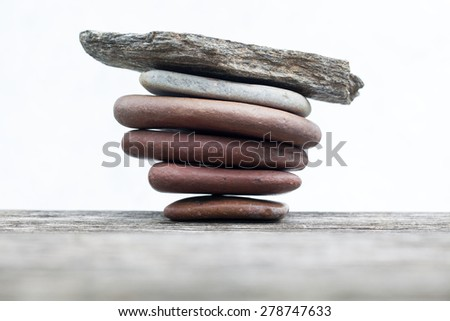 Zen stones wooden table. pile planar stones on the old wooden rustic table. - stock photo