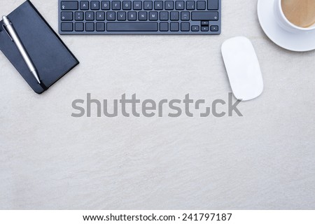 zenithal view of a business desk consisting on a wireless mouse, a cup of coffee with a coffee saucer, a keyboard, and a book calendar with a pen, on a beige desk background - suitable for copy space - stock photo