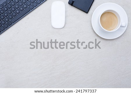 zenithal view of a closeup of a business desk consisting on a cup of coffee with a coffee saucer, a wireless mouse, a keyboard, and a book calendar on a beige desk background - suitable for copy space - stock photo