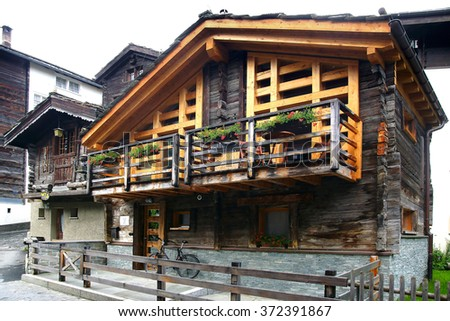 ZERMATT, SWITZERLAND - JUNE 19, 2015: The ancient traditional chalet along Oberdorfstrasse. Zermatt village dates back to the Middle Ages and today ancient barns sit alongside tastefully modern hotels - stock photo