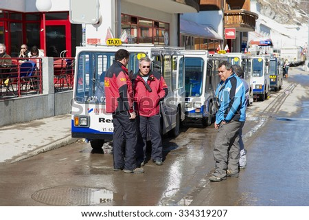 ZERMATT, SWITZERLAND - MARCH 03, 2009: Unidentified electric taxi drivers talk at the parking lot in Zermatt, Switzerland. The entire town of Zermatt is a combustion-engine car-free zone. - stock photo