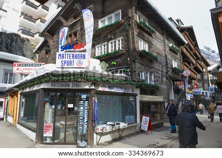 ZERMATT, SWITZERLAND - MARCH 04, 2009: Unidentified people walk by the street of Zermatt, Switzerland. Zermatt is one of the most popular ski resorts in Switzerland. - stock photo
