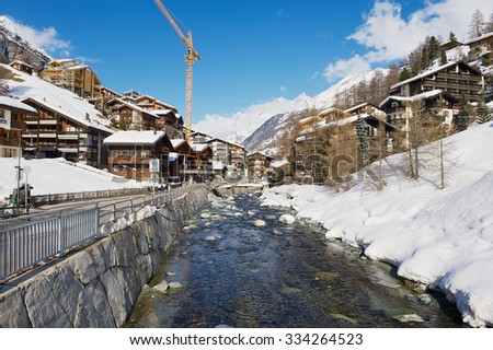 ZERMATT, SWITZERLAND - MARCH 03, 2009: View to the river and traditional houses in Zermatt, Switzrland. Zermatt is one of the most popular ski resorts in Switzerland. - stock photo