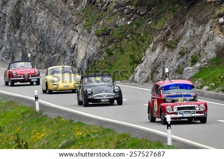 ZERNEZ, SWITZERLAND - JUNE 15: A Volvo PV544, a Daimler SP250, a Porsche 356 and a Alfa Romeo Giulia take part to the Summer Marathon on June 15, 2014 near Zernez. Cars built in 1965, 1960, 1964, 1963 - stock photo
