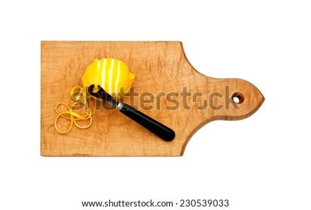 zesting a lemon on a board - stock photo
