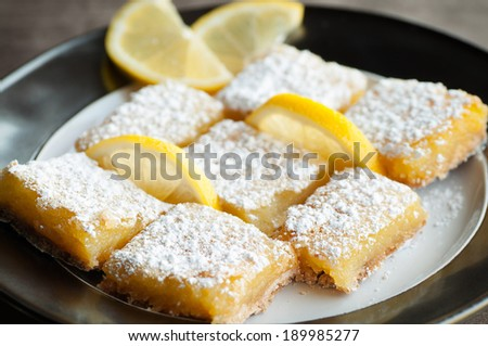 Zesty sweet lemon bars with lemon garnish and confectioner's sugar - stock photo