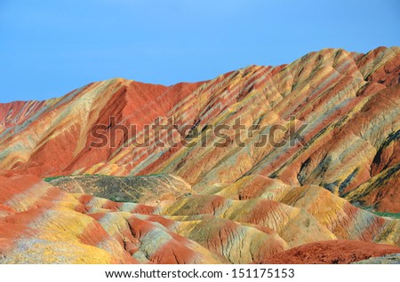 ZHANGYE, CHINA - JULY 27:  Danxia landform on July 27, 2013 in Zhangye, China. Danxia landform is formed from red sandstones and mineral deposits being laid down over twenty four million years. - stock photo
