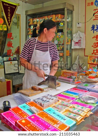 ZHOUZHUANG, SHANGHAI-SEPTEMBER 25, 2005: local lady running a cake shop.  Zhouzhuang water village is Shanghai tourist attraction with 1000000 visitors year - stock photo
