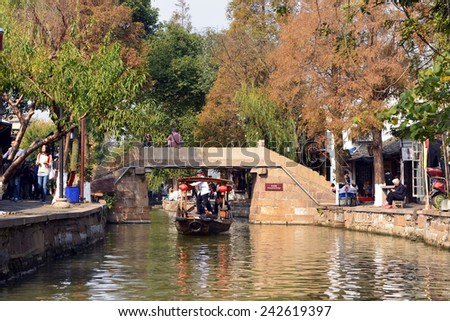 ZHUJIAJIAO, CHINA - NOV 10, 2014: Sightseeing boat take tourists on tour of the ancient water town of Zhujiajiao located in the Qingpu District of Shanghai. The streets are filled with small shops. - stock photo