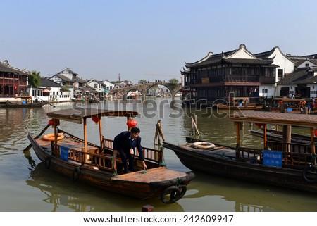 ZHUJIAJIAO, CHINA - NOVEMBER 10, 2014: Sightseeing boats ready to take tourists on tour of the ancient water town of Zhujiajiao, including Fangsheng brigde located in the Qingpu District of Shanghai.  - stock photo