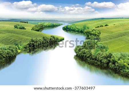 Zigzag river flows between summer valleys.a - stock photo