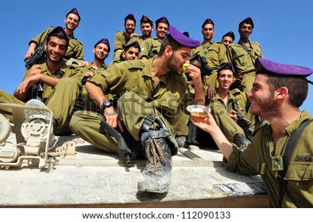ZIKIM - SEPTEMBER 07:IDF soldiers are blessing on the traditional Jewish custom of apple and honey to welcome Rosh Hasahanah, the Jewish New Year on September 07 2010 in Gaza border near Zikim, Israel - stock photo