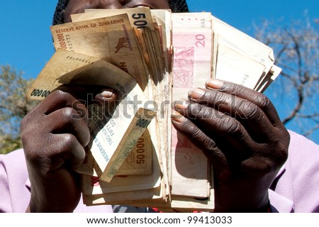 zimbabwe money being held and handled - stock photo
