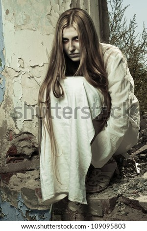 zombie girl sitting in abandoned building - stock photo