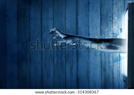 Zombie hand come out from television. Halloween concept - stock photo