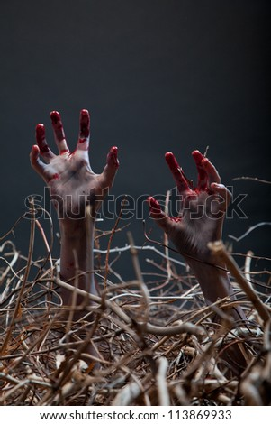 Zombie stretching his creepy hands from the grave, Halloween theme - stock photo