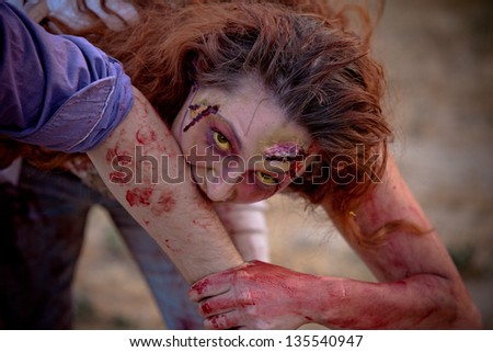 Zombie woman outside with yellow eyes looking at camera biting a victim - stock photo