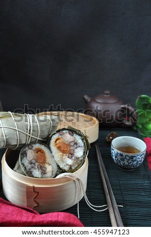 Zongzi Chinese traditional food with hot tea set on dark background - stock photo