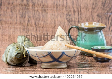 Zongzi or sticky rice dumpling (Chinese Rice Dumplings food) with teapot for dragon boat festival - stock photo