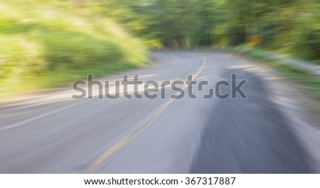 Zoom blur high speed motion at the curve road in  countryside for abstract background. - stock photo