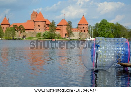 Zorbing air bubbles on water. Trakai Castle surrounded by lake Galve. XIV - XV century architecture in Lithuania. - stock photo