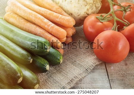 Zucchini, carrots, celery root and tomatoes on wooden table. Processed with soft light sun glow effect. Copy space