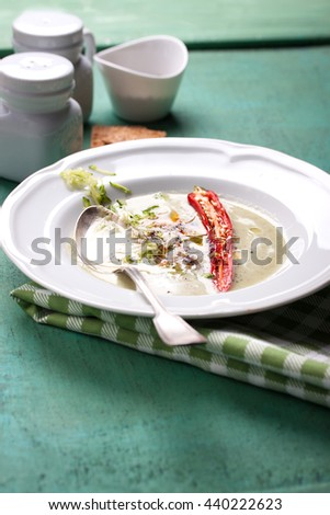 Zucchini cream soup with red pepper, cream, spices and balsamic cream on a wooden background - stock photo