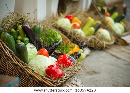 Zucchini, peppers, eggplants and cabbages in basket with straw on city market - stock photo