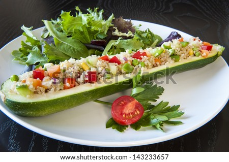 Zucchini stuffed with quinoa and vegetables on a white plate - stock photo