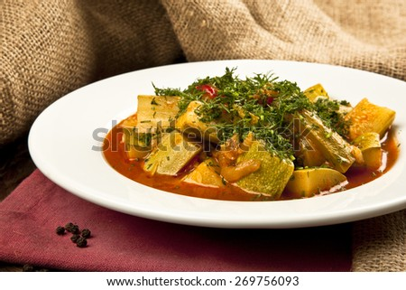 Zucchini vegetable casserole with dill weed in a plate on table - stock photo