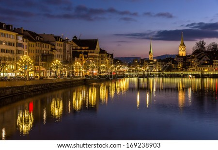 Zurich on banks of Limmat river at winter evening - stock photo