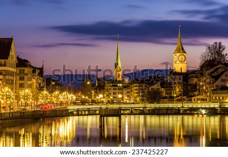 Zurich on banks of Limmat river on a winter evening - stock photo