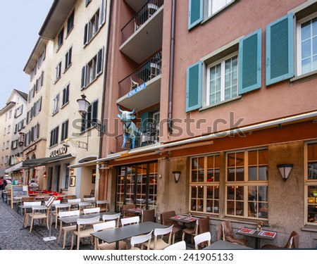 ZURICH, SWITZERLAND - APRIL 19, 2014: Cow sculpture on balcony of the hotel Adler at city historical center in Zurich on April 19, 2014. Cowbell on its neck is one of symbols of Switzerland  - stock photo