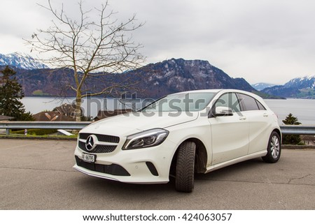 Zurich, Switzerland. March 10, 2016. Beautiful white Mercedes parked by the side of the road in the mountains. - stock photo