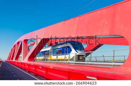 ZWOLLE, NETHERLANDS - NOVEMBER 1, 2014: Dutch railways train passing the new red railroad bridge over the IJssel river in the Netherlands - stock photo