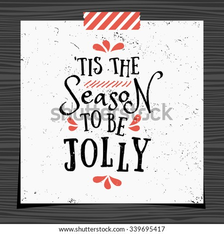 Christmas typographic design greeting card template. 'Tis the Season to be Jolly message in black and red on white background. Christmas card with a strip of washi tape on dark wood background. - stock vector