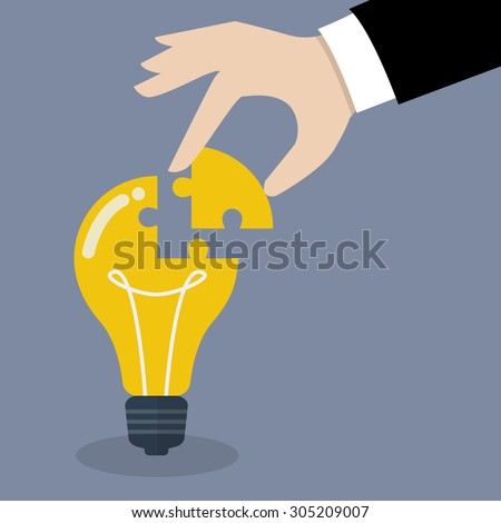 Hand inserts the missing puzzle in lightbulb. Business idea concept - stock vector